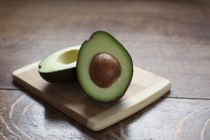 Two halves of a cut avocado with seed on a small cutting board sitting on a wooden surface.