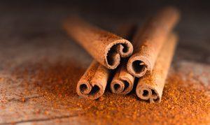 Cinnamon sticks sprinkled with ground cinnamon on a textured surface.