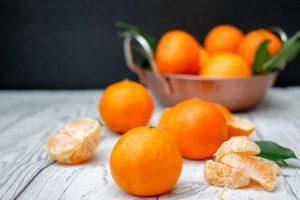 Whole oranges, peeled orange slices, and orange leaves on marble counter top with bowl of oranges in background.