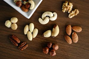 Mixed nuts (almonds, cashews, Brazil nuts, pecans, hazelnuts, walnuts, and macadamia nuts) on wooden table.